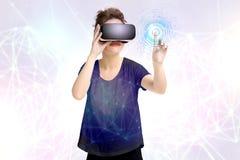 A moça que obtém a experiência usando vidros dos auriculares de VR, é monóculos aumentados da realidade, estando em uma realidade Foto de Stock Royalty Free