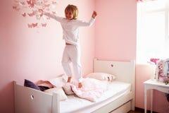 A moça que salta em sua cama Fotografia de Stock Royalty Free