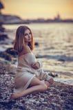 Moça que senta-se na praia após o por do sol no fundo do mar Imagens de Stock