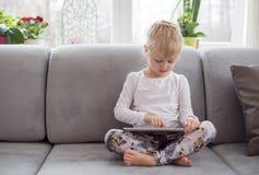 Moça que senta-se no sofá e que usa o tablet pc Imagens de Stock