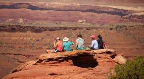 MOAB, ЮТА, 15-ое апреля 2017 - молодые туристы сидят на уступе утеса около Moab, Юты Стоковые Фотографии RF