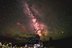 An SUV under the bright Milky Way galaxy stars, Moab Utah. Moab, Utah - 6/12/16 - A beautiful desert starry night in Moab Utah. Milky Way galaxy astrophotography stock photos