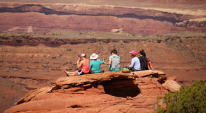 MOAB, UTAH, le 15 avril 2017 - les jeunes touristes s'asseyent sur un rebord de roche près de Moab, Utah Photos libres de droits