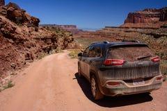 Moab Utah, USA - Juni 15, 2015: Jeep Cherokee på en vit väg för kantvägShafer slinga i den Canyonlands nationalparken arkivfoton