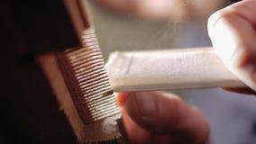 Moagens do artesão um pente de madeira manualmente com fim de lixamento do papel acima Vista inferior 4 K video estoque