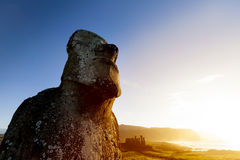 Moai with blue and orange. Moai looking at sea with bright blue sky and orange sea in background Royalty Free Stock Photo