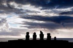 Moai fem i silhouette i påskön Arkivbild