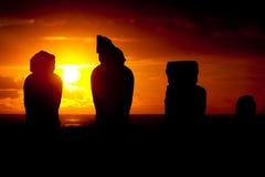 Moai fyra mot dramatisk solnedgång i påskön Arkivbild