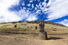 Moais in the hill in Easter Island. Partly buried moais in hillside and soft clouds in bright bule sky in Easter Island stock image