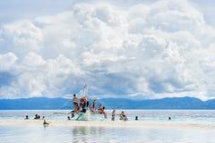 Moalboal cebu philippines - 24-ое июня 2016: Азиатские люди при туристы получая потеху и остатки на шлюпке в тропическом море Стоковое Фото