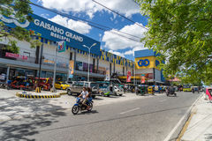 Moalboal. Cebu. Philippines - 03 april 2016: Mall Gaisano under blue sky near parking and road with motorcycle. Bus and tricycle Stock Images