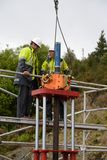 Removing the casing. MOANA, NEW ZEALAND, OCTOBER 27, 2017: Engineers discuss how to set up a huge hydraulic jack on top of an old oil well to remove the steel Stock Image