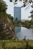 The moat of Osaka Castle with modern buildings in the distance Stock Photo