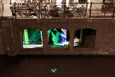 Moats art. Light art in the city of Utrecht at a moat with bicycles above it on the street Royalty Free Stock Image