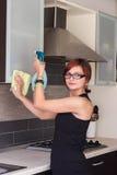 Mobília da limpeza da moça na cozinha Fotografia de Stock