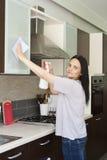 Mobília da limpeza da mulher adulta na cozinha Imagens de Stock Royalty Free