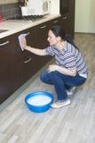 Mobília da limpeza da mulher com espuma na bacia Fotografia de Stock