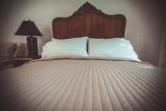 Mobília de madeira da cama da teca clássica no quarto morno e acolhedor, ne foto de stock