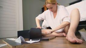 A mobília de montagem em casa, uma dona de casa monta uma mesa do computador usando ferramentas da mão