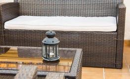 Mobília do Rattan, poltronas do sofá, mesa de centro de vidro com castiçal, fragmento do pátio, patamar, mediterrâneo Fotografia de Stock Royalty Free