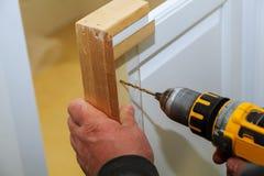Mobília e brocas de montagem a porta de armário usando a chave de fenda imagem de stock royalty free