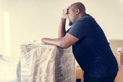Mobília movente do homem negro dentro à casa nova fotos de stock