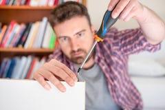Mob?lia de montagem do homem em casa no assoalho imagem de stock