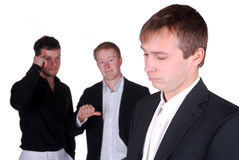Mobbing. Businessman is sad while two colleagues talks over him Stock Image