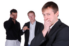 Mobbing. Businessman is sad while two colleagues talks over him Royalty Free Stock Image