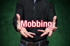 Mobbing, bullying, man holds lettering in the hands Royalty Free Stock Photo