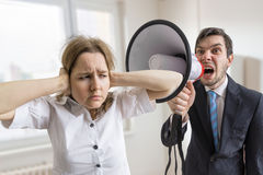 Mobbing at work. Manager is shouting at his secretary at work with megaphone Royalty Free Stock Images