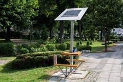 Mobiel zonnepaneel op de bank in openbaar park voor batterij het laden stock afbeeldingen