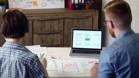 Mobiele app ontwerpers die de lay-out van de smartphonetoepassing ontwikkelen en hoogte vijf geven stock videobeelden