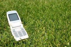 Mobiele celtelefoon op gras buiten Stock Afbeeldingen