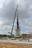 Mobiele die kraan aan het opheffen van zwaar materiaal bij bouwwerf wordt gebruikt Stock Foto's