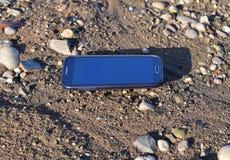 Mobiele die telefoon op het strand wordt verloren Stock Afbeelding