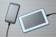 Mobiele slimme telefoon en tabletpc die op zilveren bureau laden royalty-vrije stock foto's
