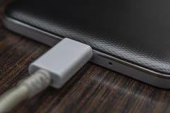 Mobiele slimme telefoons die op houten bureau laden stock fotografie