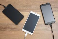 Mobiele slimme telefoons die op houten bureau laden Stock Foto
