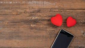 Mobiele smartphone met het zwarte scherm en twee rode harten op houten geweven achtergrond, lege exemplaarruimte Vlak leg, hoogst royalty-vrije stock fotografie
