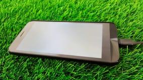 Mobiele telefoon die op groene grasachtergrond laden Stock Afbeelding