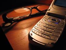 Mobiele telefoon en glazen op het bureau Stock Fotografie