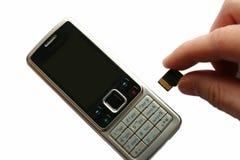 Mobiele telefoon en hand met geheugenkaart Stock Afbeelding