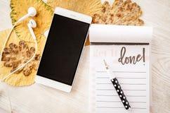 Mobiele telefoon, hoofdtelefoons en nota over rustieke lijst met bladeren Stock Foto