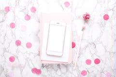 Mobiele telefoon met een roze notitieboekje met roze decoratie op een marmeren achtergrond stock afbeelding