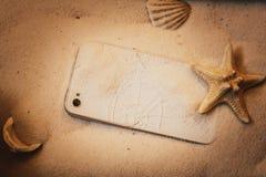mobiele telefoon met het gebroken scherm in het zand stock fotografie