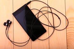 mobiele telefoon met paar van oortelefoon Stock Foto