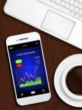 Mobiele telefoon met voorraadgrafiek, mok koffie en laptop toetsenbord Stock Foto