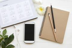 Mobiele telefoon, notitieboekje van student het schrijven nota voor studie stock afbeelding