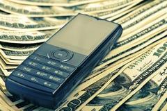 Mobiele telefoon op het geld Stock Afbeeldingen